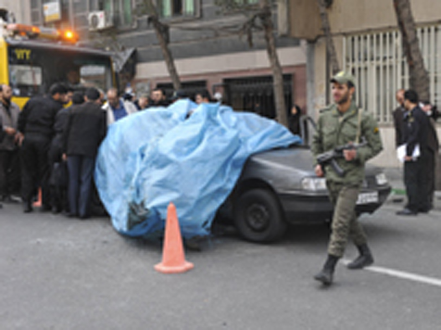 A policeman walks past the car belonging to Iranian nuclear scientist Mostafa Ahmadi-Roshan at a blast site in Tehran