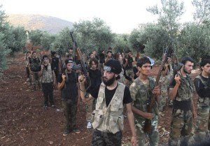 Free Syrian Army fighters, holding their weapons, stand during military training north of Idlib