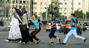 A young Egyptian man grabs a woman crossing the street with her friends in Cairo. Vigilante groups are now taking to the streets and spray-painting the clothes of the harassers.