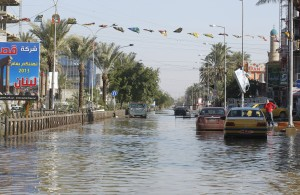 Cars are seen along a flooded street after overnight rain in Baghdad