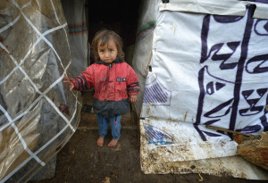 CHILD STANDS OUTSIDE MAKESHIFT SHELTER AT REFUGEE CAMP IN LEBANON