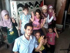 Aeham Ahmad e il coro dei germogli di Yarmouk davanti al bellissimo pianoforte - fonte Facebook locale